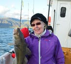 A traveller showcasing their catch of the day with pride, on a fishing tour from Reykjavík Harbour in Iceland.