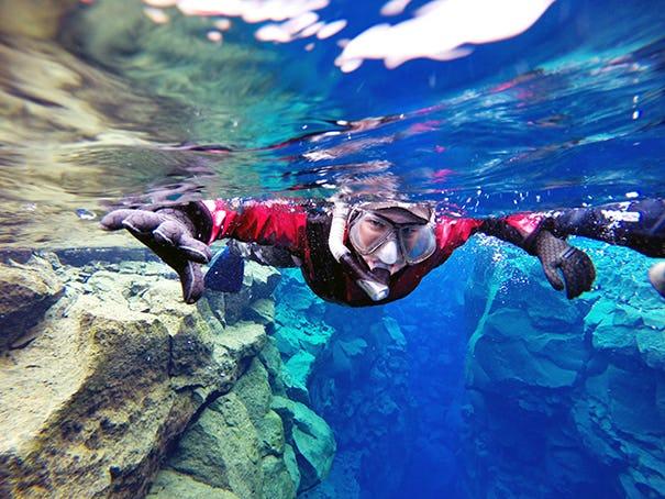 Dzięki suchemu skafandrowi możesz spokojnie unosić się na powierzchni wody podczas snorkelingu w szczelinie Silfra.