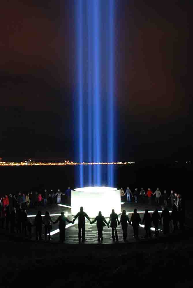 A group bonds at the Imagine Peace Tower over the message of Yoko Ono and John Lennon.