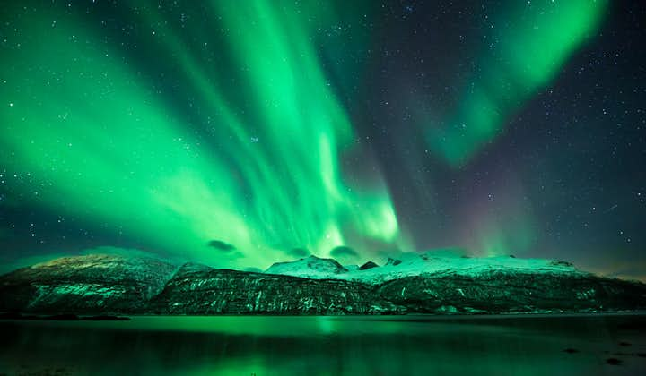 An intense display of green Northern Lights over West Iceland in winter.
