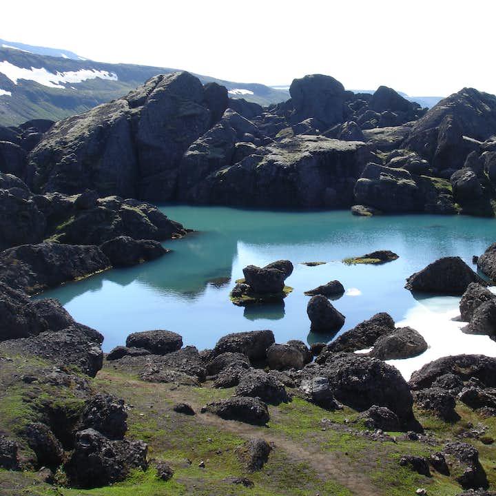 A lake in Stórurð surrounded by black boulders