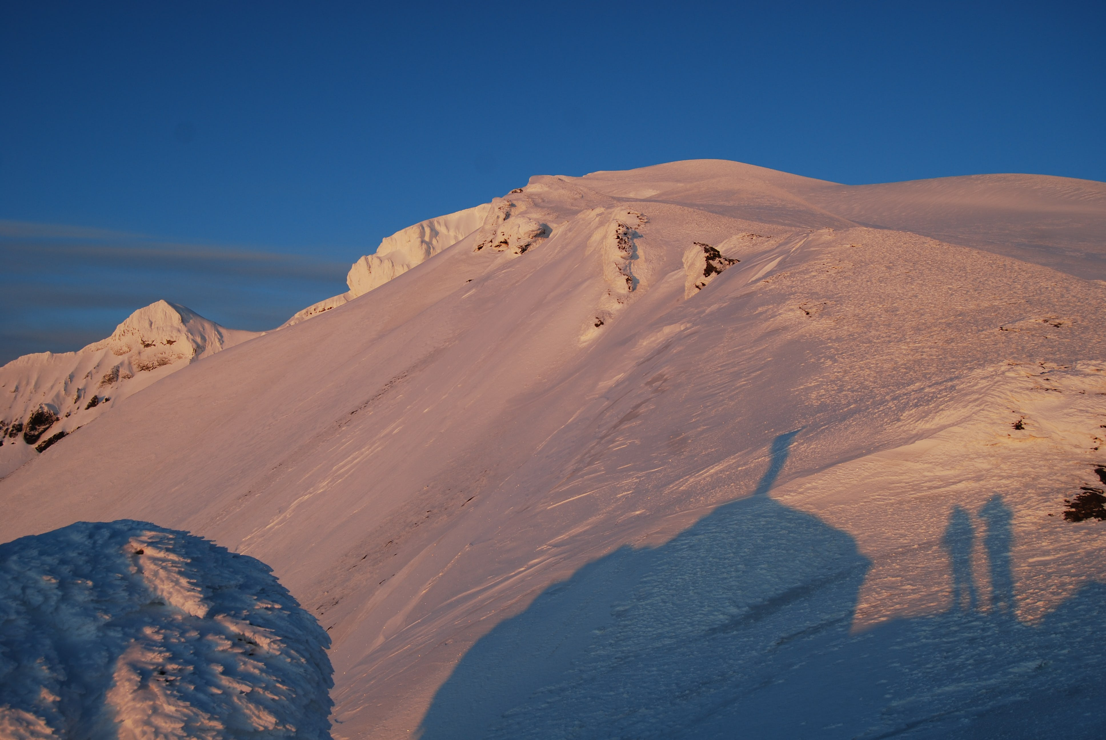 The midnight sun casting its golden glow on the snow-drenched hills of Mt. Snæfell.