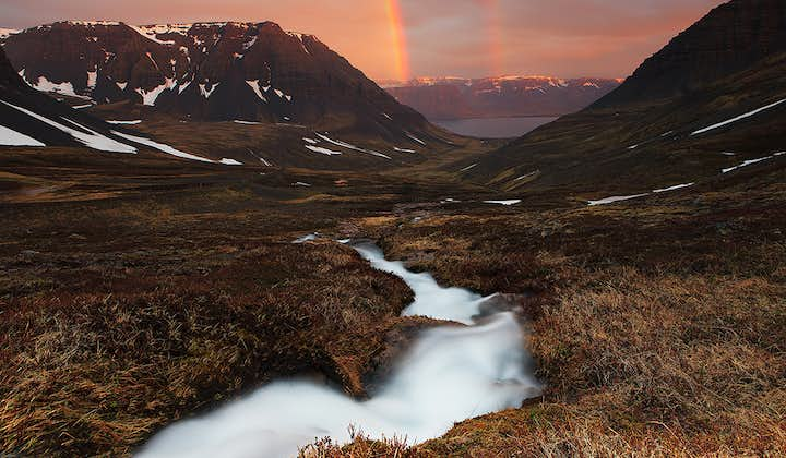 A twin rainbow arches over a fjord of the Westfjords, on a day of sun and shine in Iceland's summer.