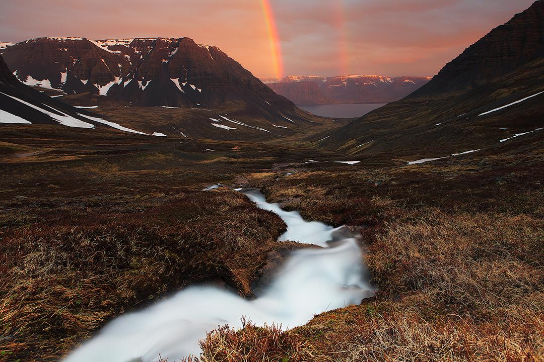 Un arcobaleno gemello si inarca su un fiordo, in un giorno di sole e splendore dell'estate islandese.