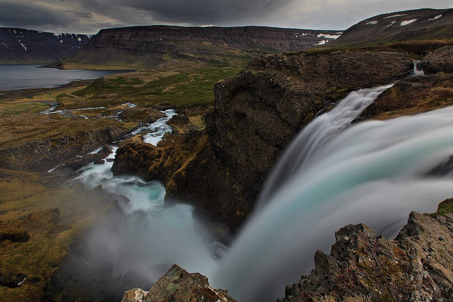 River flows down the mountainside in one of Westfjords beautiful fjords