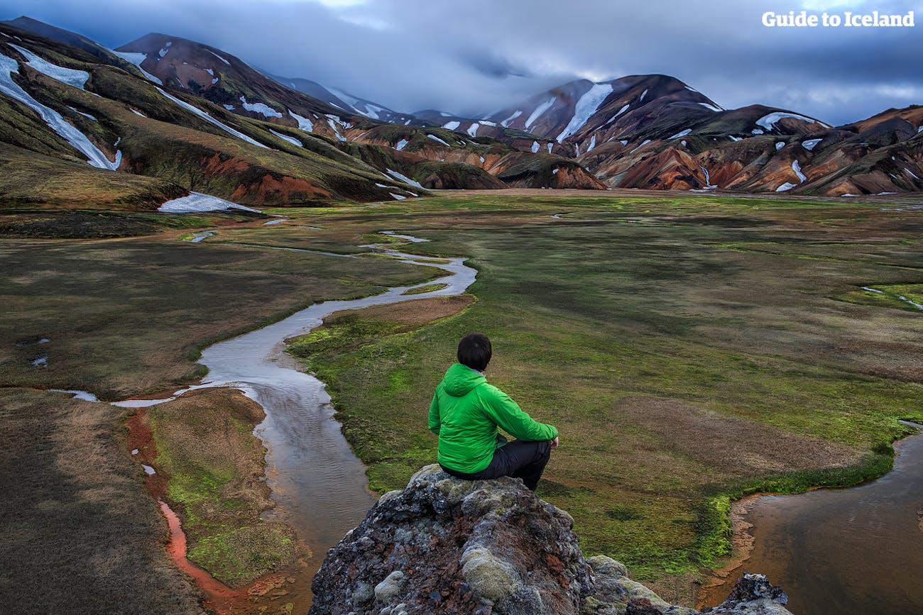 Mężczyzna siedzący patrzący na krajobraz w Landmannalaugar