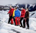 A group carefully appreciates a crevasse in Sólheimajökull in winter.