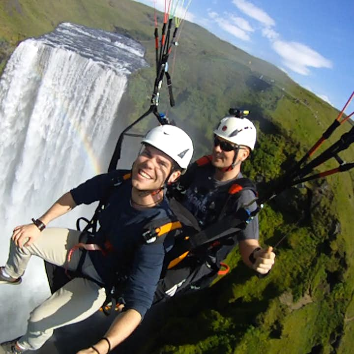 Soaring past the mighty Skógafoss waterfall on a paragliding tour on the South Coast.