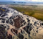 A river system snakes across black sands in south Iceland to the ocean.