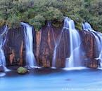 Das Wasser des Wasserfalls Hraunfossar rinnt über die schwarze Lava herab.