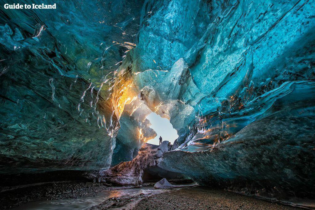 ヴァトナヨークトル国立公園にある青一色の氷の洞窟に差し込んだ太陽が氷の色を金色に変える
