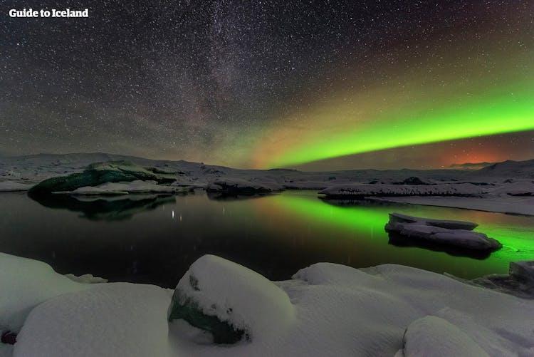 초록과 보라 색의 아름다운 오로라가 요쿨살론 빙하 호수에서 춤을 춥니다.