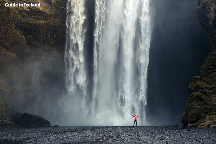 An observer walking right up to the cascading water at Skogafoss.