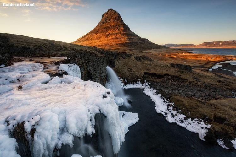 Mount Kirkjufell, behind the frozen waterfall Kirkjufellsfoss.