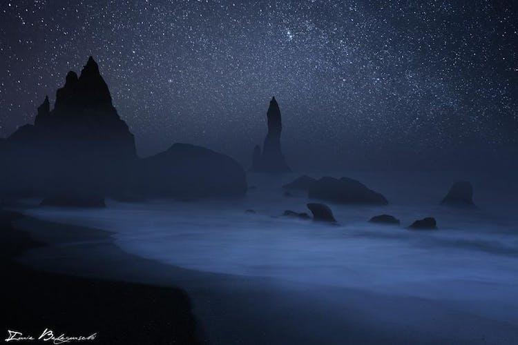 ชายฝั่งทางใต้ของประเทศไอซ์แลนด์ช่วงกลางคืนดูลึกลับและสวยงามด้วยการก่อตัวของหินสีดำที่ดูน่ากลัว