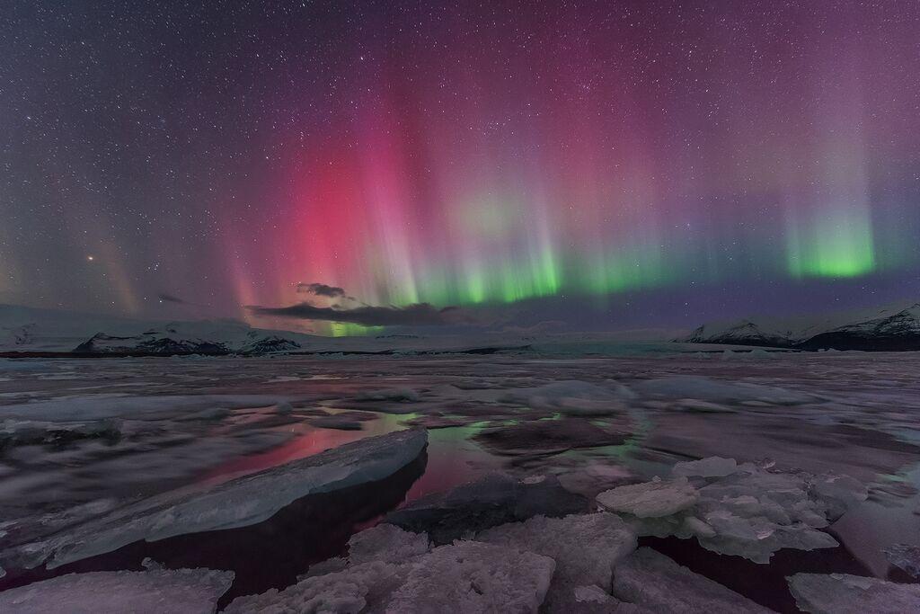 Zorza polarna wypełnia niebo i farbuje otoczenie swoimi kolorami, szczególnie przy lagunie lodowcowej Jökulsárlón.
