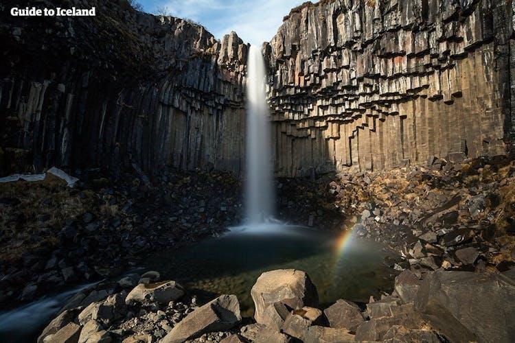 柱状節理に囲まれたスヴァルティフォスの滝は、アイスランド語で黒い滝という意味の名だ
