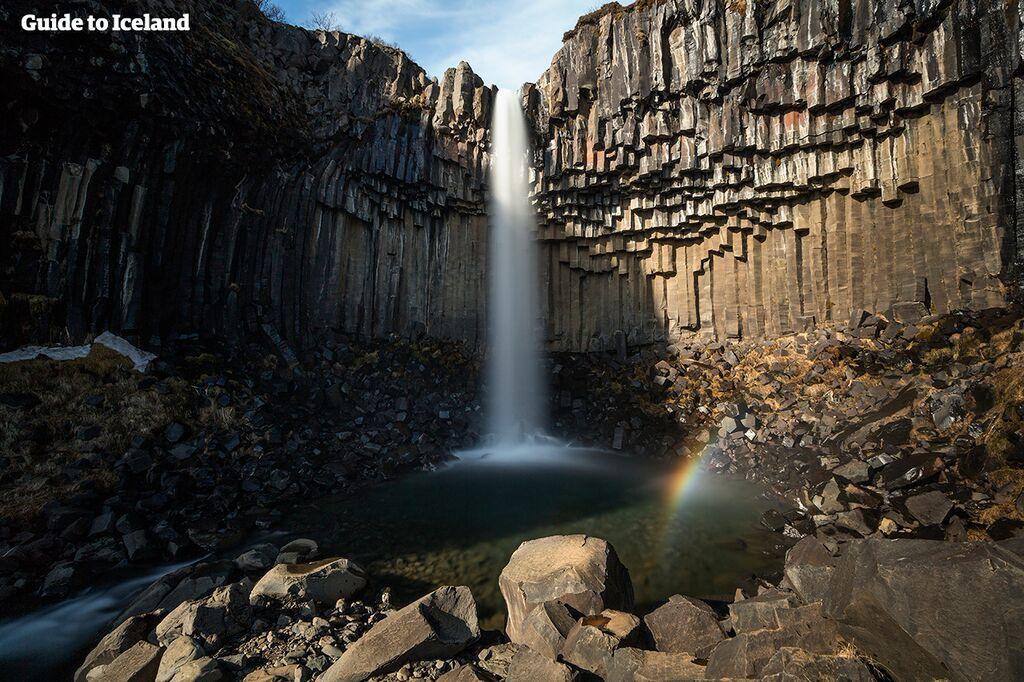 """Ciemne klify sześciokątnych kolumn bazaltowych nadają nazwę Svartifoss - """"Czarny wodospad""""."""