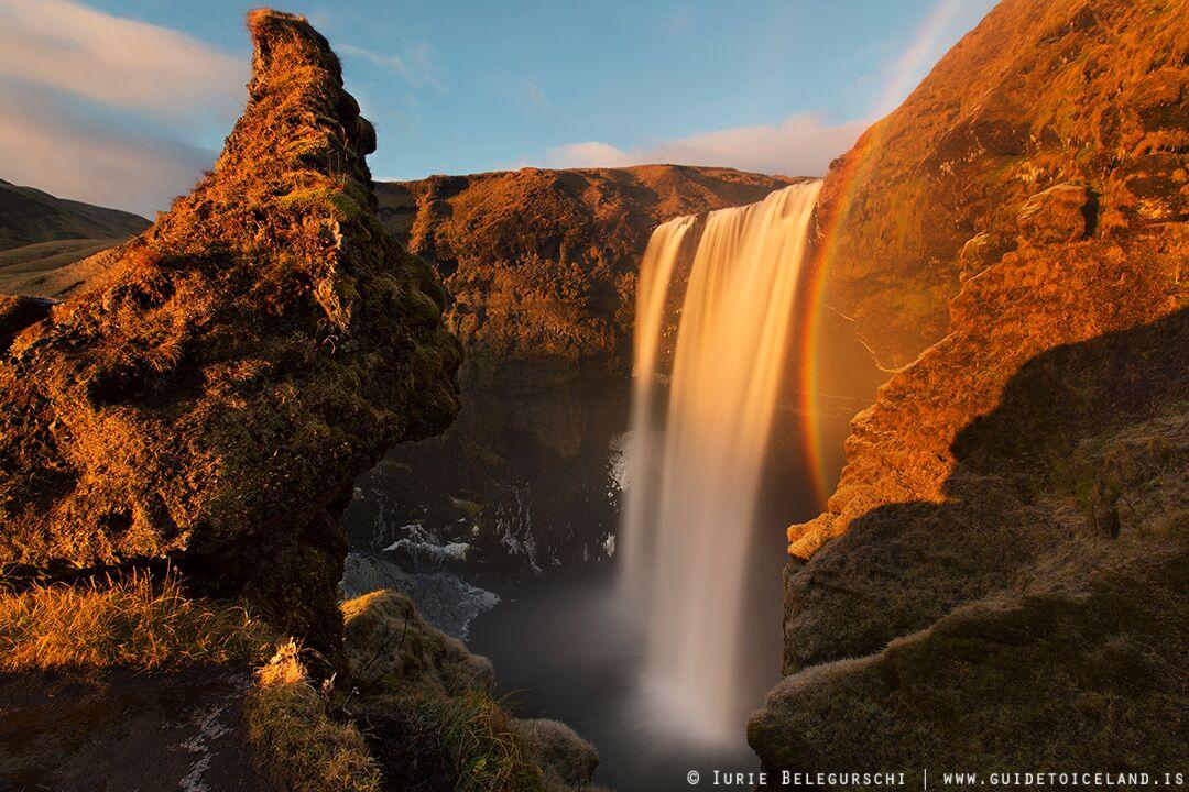 En el resplandor veraniego del sol, un arcoiris está constantemente presente en la niebla de la cascada de Skógafoss.