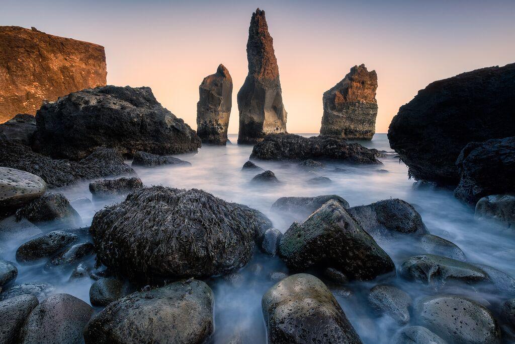 Пляж с черным песком Рейнисфьяра расположен в окружении драматических скал.