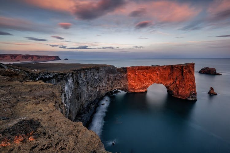 Dyrhólaey is a rock arch, pictured here pink under the light of the midnight sun.
