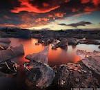 Der rote Nachthimmel unter der Mitternachtssonne spiegelt sich wunderschön im Wasser der Gletscherlagune Jökulsárlón.