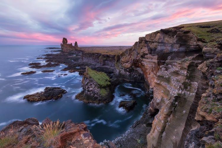 Il mare di basalto di Lóndrangar si raccoglie sotto il sole di mezzanotte, nell'Islanda occidentale.