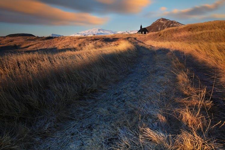 Un camino en la península de Snæfellsnes conduce a la iglesia Buðir y, más allá, al glaciar Snæfellsjökull.