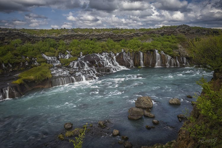 Hraunfossar waterfall streams out of a wide lava field in east Iceland in many serene rivulets.