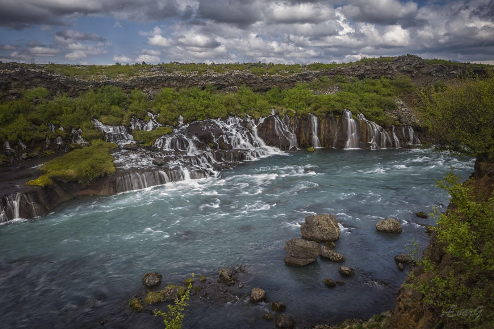La cascada Hraunfossar brota de un amplio campo de lava en el este de Islandia en muchos riachuelos serenos.