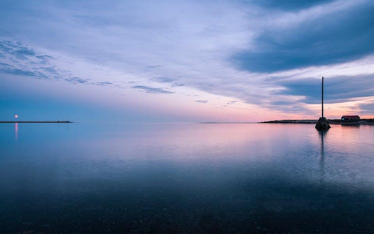 A perfectly flat seas blurs into the sky on a midsummer's night from a harbour in Iceland.