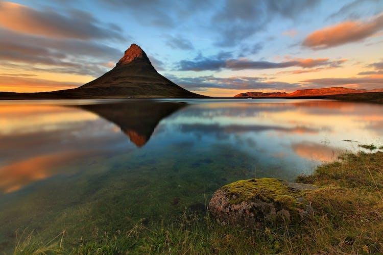 ภูเขาเคิร์คจูแฟสสะท้อนอยู่บนผิวน้ำท่ามกลางคืนในฤดูร้อนในไอซ์แลนด์