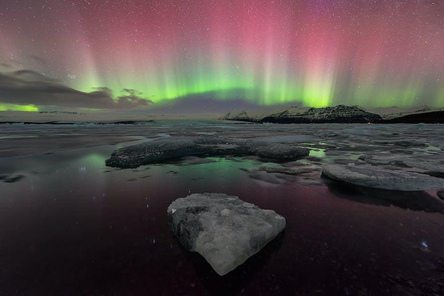 冰岛杰古沙龙冰河湖北极光,被绿色和粉色点亮
