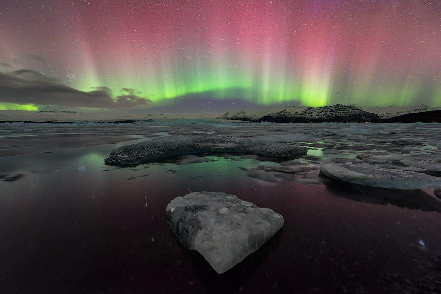 ヨークルスアゥルロゥン氷河湖の空に舞い踊るオーロラ