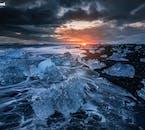 La plage de Diamant, dans le sud-est de l'Islande, est un lieu de couleur contrastée, avec de la glace bleue, du sable noir, du blanc et un ciel rouge sang en hiver.