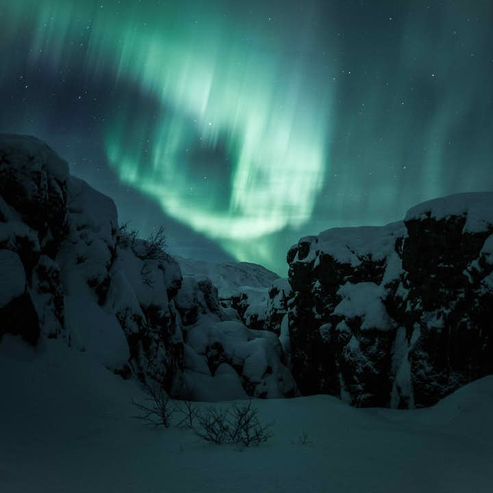 The aurora borealis dancing over Iceland's winter landscapes.