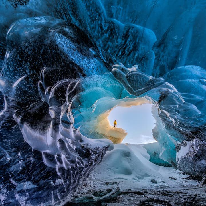 A bright winter's day is visible through the entrance of one of Vatnajökull's crystal blue ice caves.