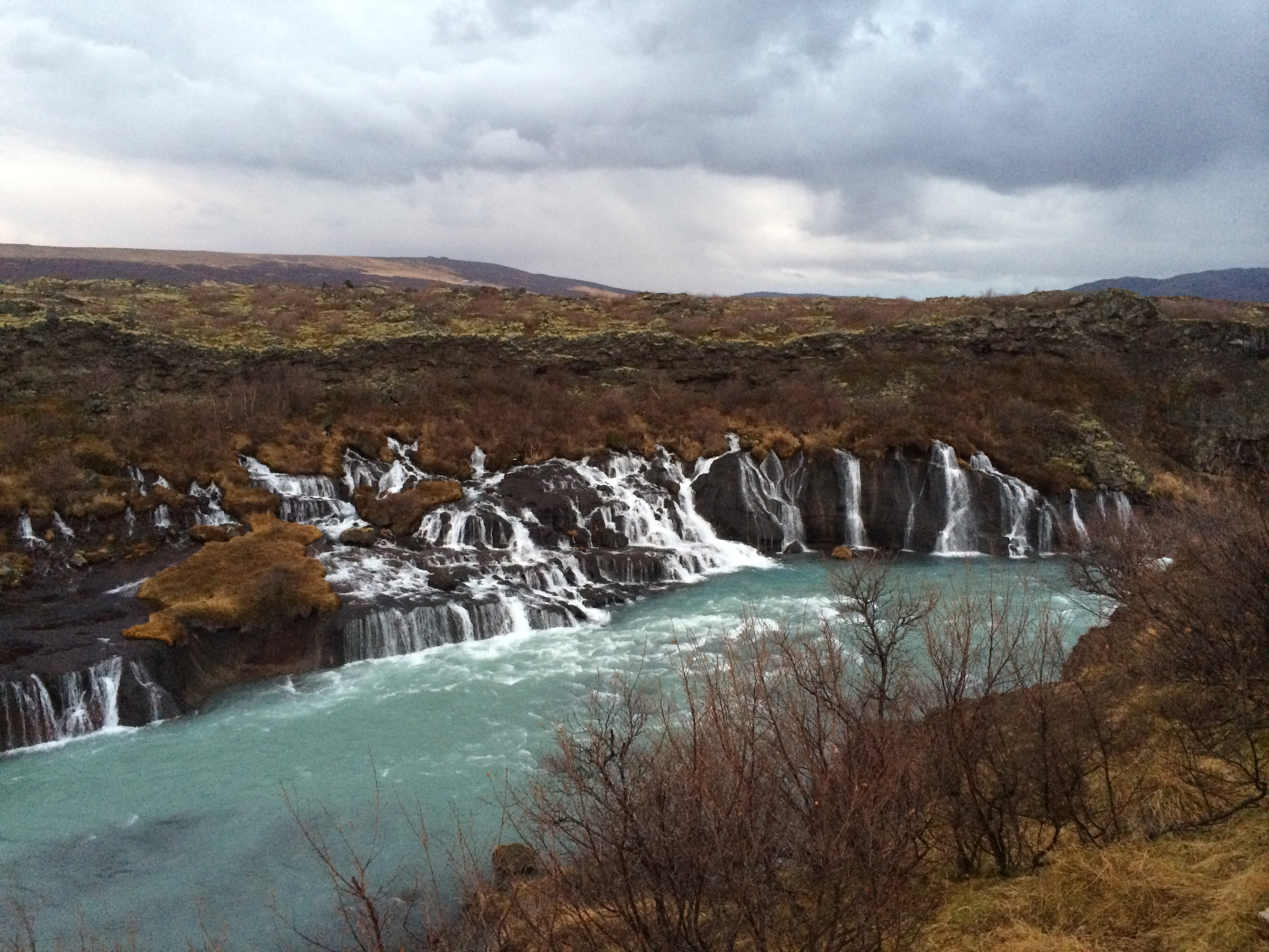 Hraunfossar waterfalls create a sheet of small rivulets, streaming down the lava wall.