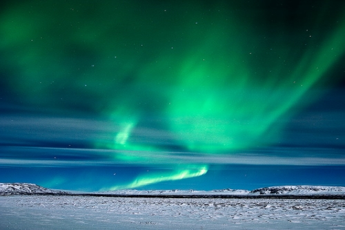 Auroras dancing over a snowy landscape in Iceland.