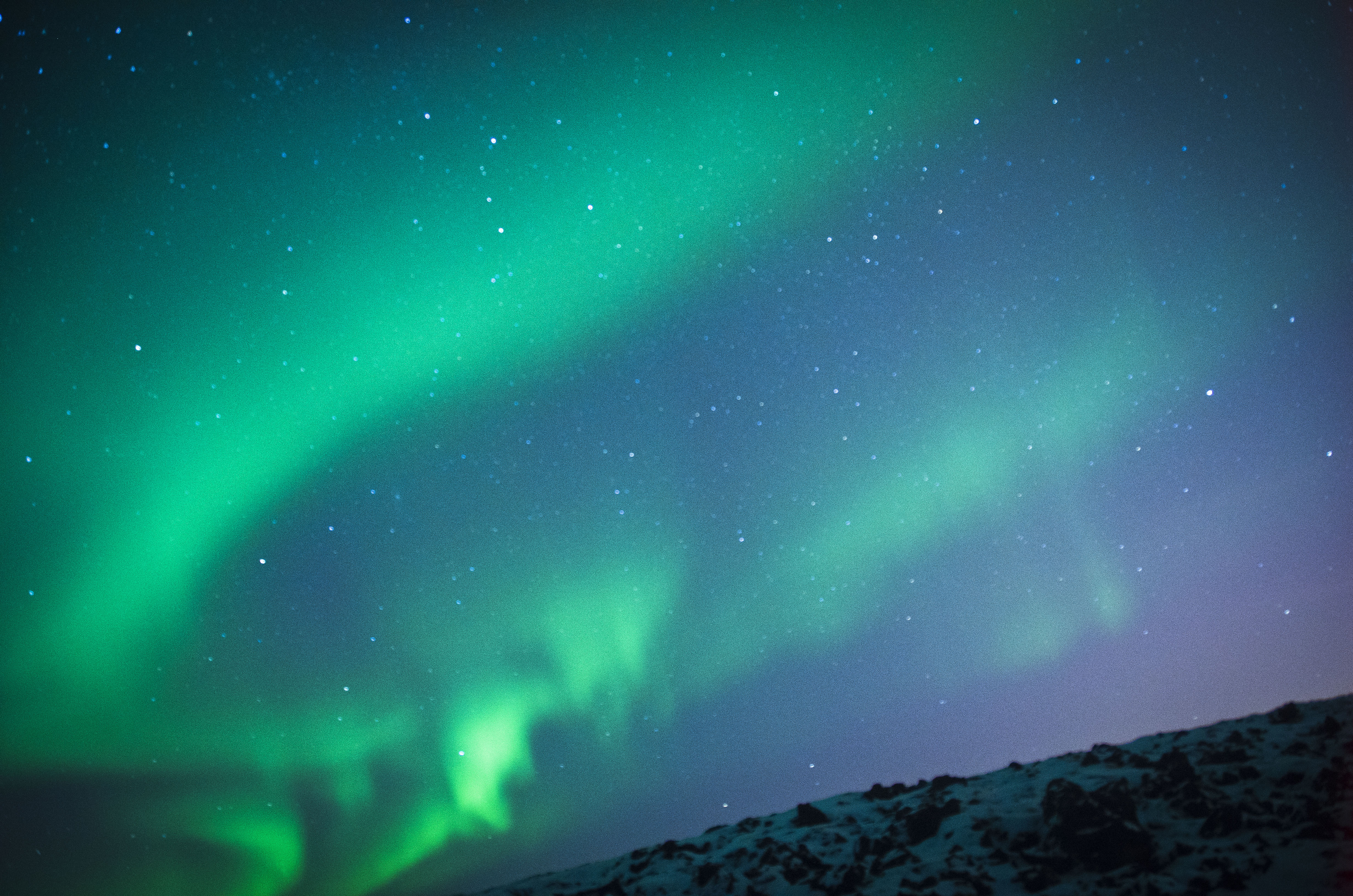 An ethereal sky of infinite stars and descending aurora lights in west Iceland's winter.