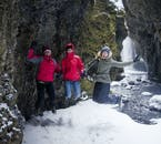 A group of winter travellers in Nauthúsagil crevice in South Iceland.
