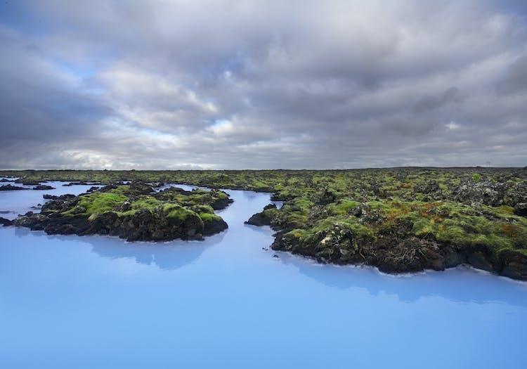 Lazurowe wody i szmaragdowy mech ujawniają kontrasty Błękitnej Laguny na półwyspie Reykjanes.