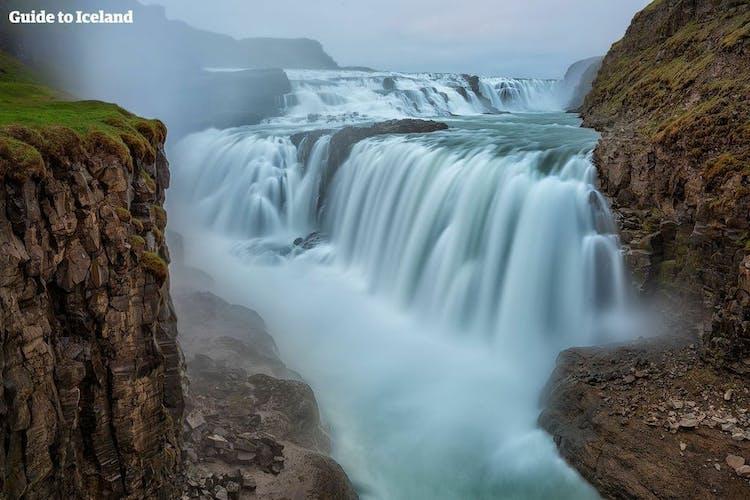 Wodospad Gullfoss spada szeroką kaskadą do ciemnego, głębokiego kanionu.