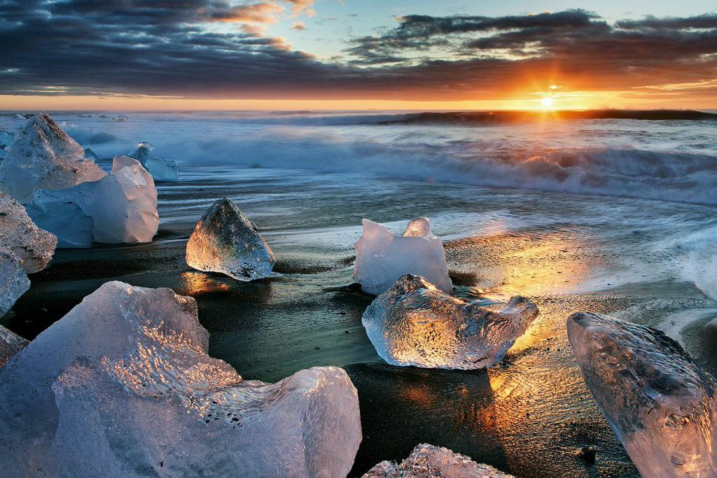 พระอาทิตย์เที่ยงคืนสาดแสงสวยลงบนหาดไดมอนด์บีชในทางใต้ของไอซ์แลนด์