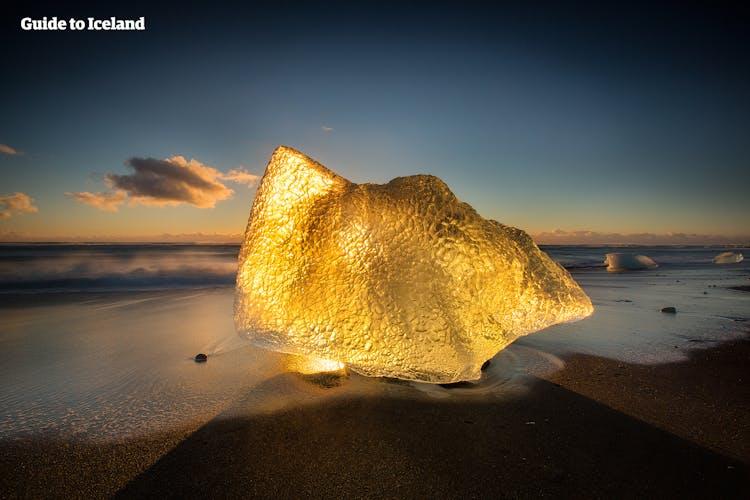 Ein Eisbrocken am Diamantstrand wird vom Licht der tiefstehenden Mitternachtssonne berührt.