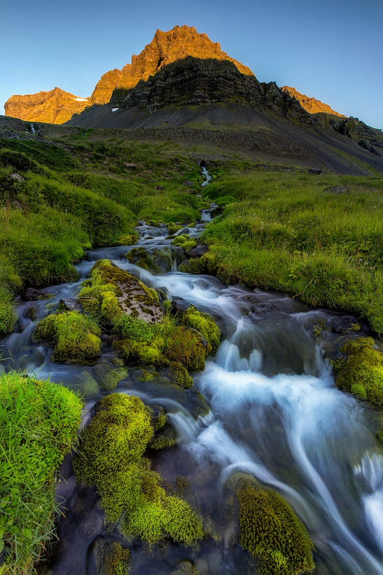 From a jagged mountain peak on the Snæfellsnes Peninsula, a charming stream runs through a field of moss.