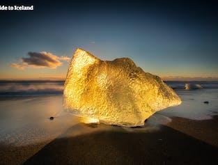 Złota poświata oświetla górę lodową na południowym wybrzeżu Islandii na niesamowitej czarnej plaży.