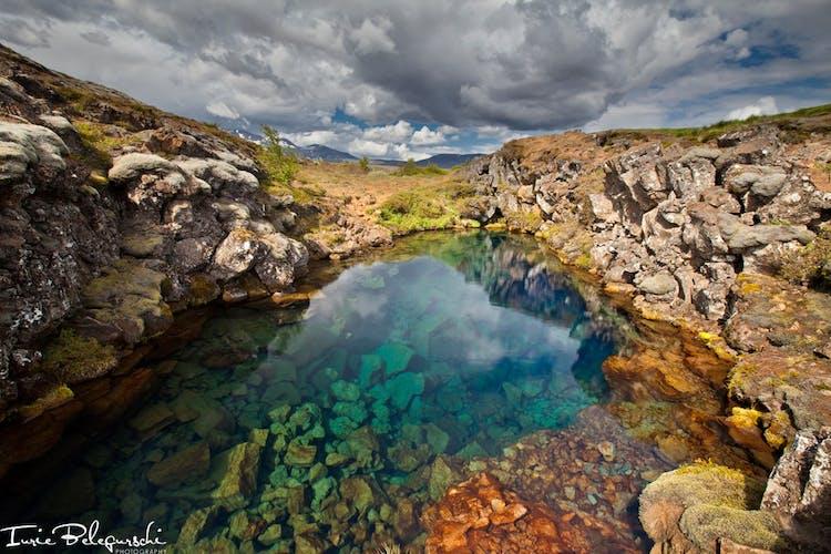 Schmelzwasser vom Gletscher Langjökull sickert in ein Lavafeld und fließt unterirdisch zu den Erdspalten im Nationalpark Þingvellir; durch diesen langen Filtrationsprozess haben die Quellen hier das ganze Jahr über eine weltweit einzigartige Sichtweite.