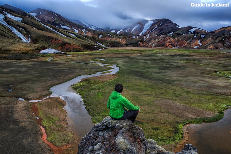 A hiker in Landmannalaugar takes a break at one of the Highland Reserve's beautiful vantage points, to take in summer views of its mountains, rivers and mossy lava fields.