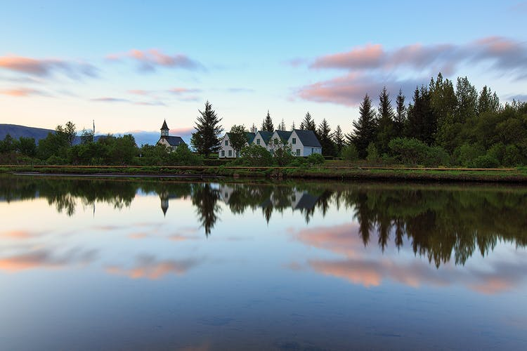 At Þingvellir National Park, visitors can discover historical buildings, glacial springs, waterfalls, towering cliff faces and dried magma fields.